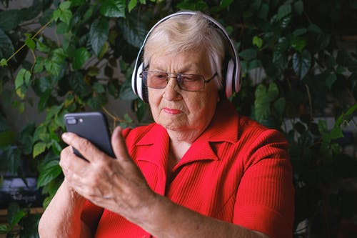 Focused aged woman browsing smartphone while listening to song