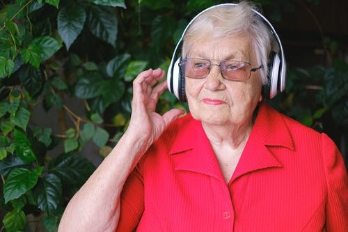 Senior thoughtful female in eyeglasses and wireless headphones listening to music near green leaves