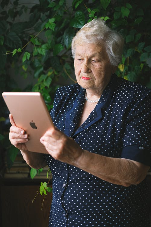 Elderly woman browsing modern tablet in garden