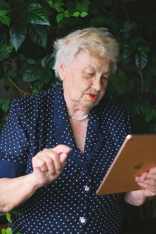 Aged smart female working online and surfing internet while using tablet in garden