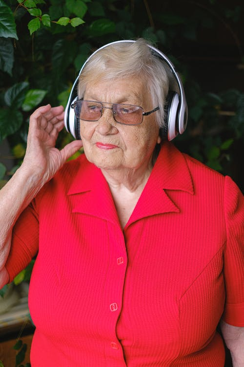 Elderly dreamy female touching wireless headphones while listening to music and looking away in garden