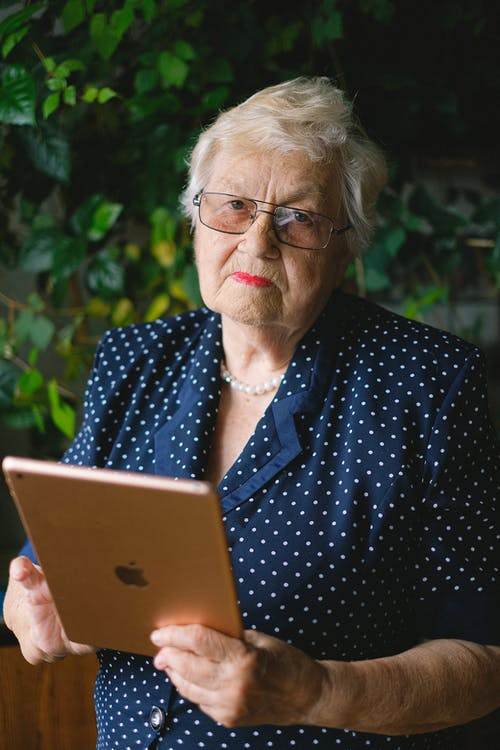 Aged woman with modern tablet in hands