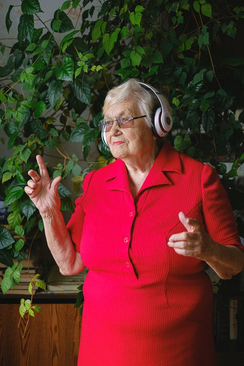 Elderly cheerful female in bright red dress and headphones listening to music while dancing and looking away near green plant