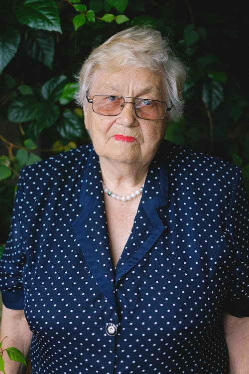 Aged woman in eyeglasses and polka dot dress