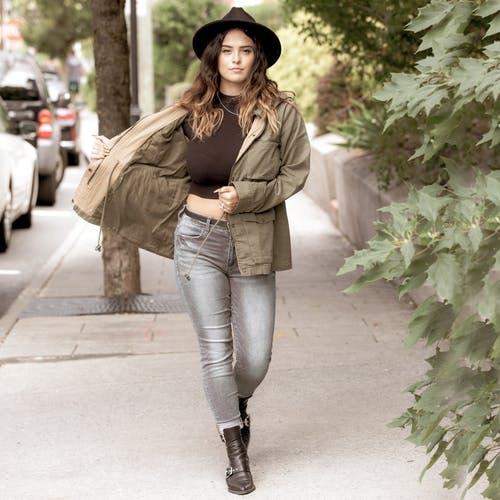 Woman in trendy hat and parka walking on street