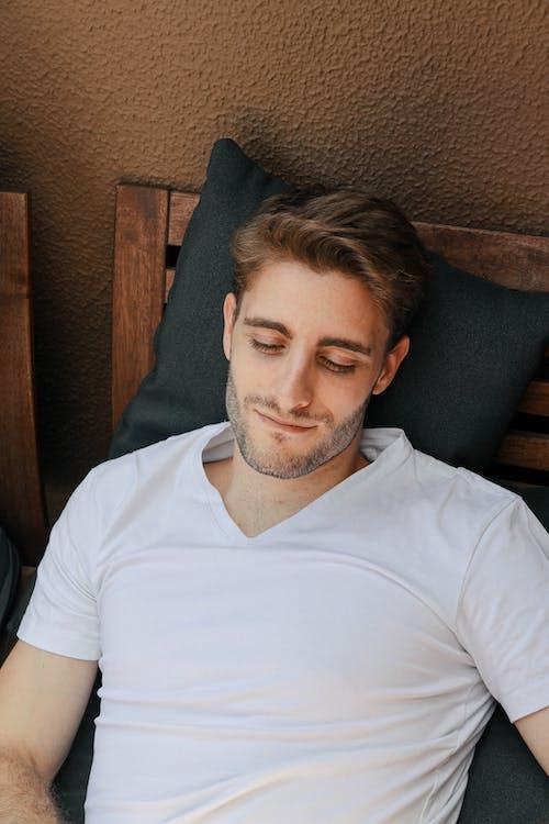 Man in White Crew Neck T-shirt Sitting on Gray Sofa