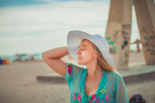 Woman in Blue and Pink Floral Shirt Wearing White Sun Hat