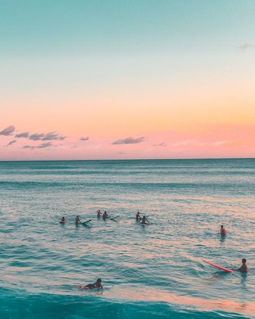 People Surfing in Sea Water