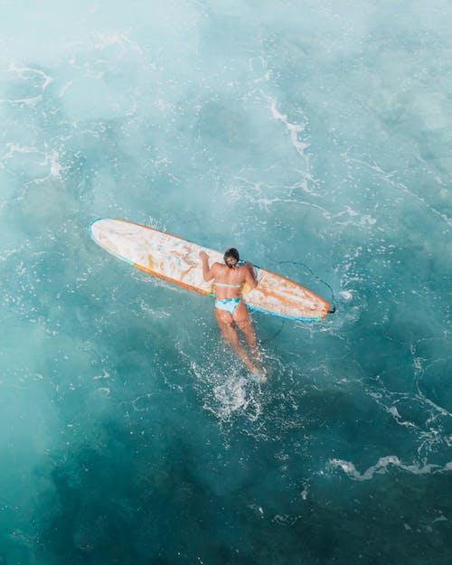 Woman in Blue Bikini Surfing in the Ocean