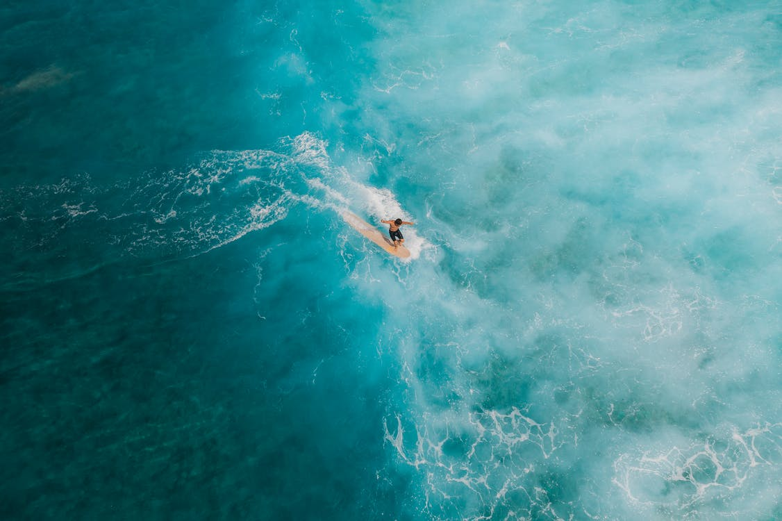 Person Surfing on Blue Water