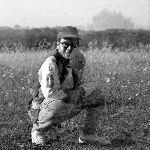Grayscale Photo of Man in White Long Sleeve Shirt and Black Pants Sitting on Grass Field