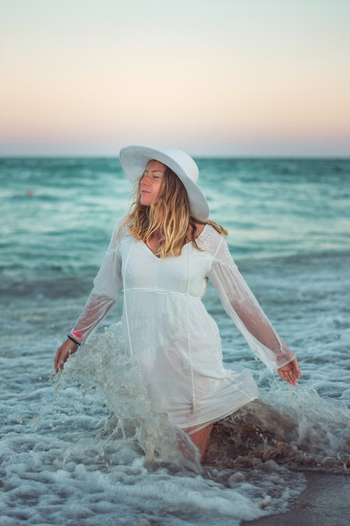 Woman in White Long Sleeve Dress Sitting on Rock by the Sea