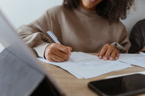 Close-Up Shot of a Person Writing on a Paper Using a Ballpen