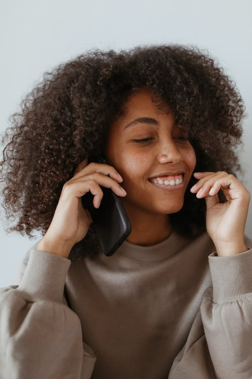 Woman in White Sweater Holding Black Telephone