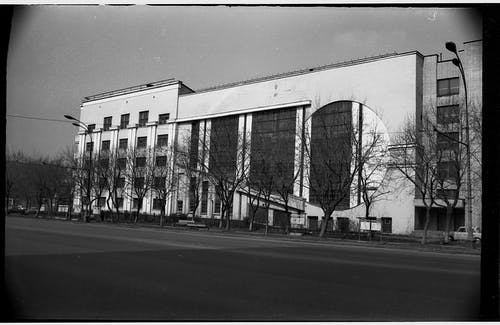 Black and white of aged multistory garage building with symmetric windows located near empty asphalt road in Moscow