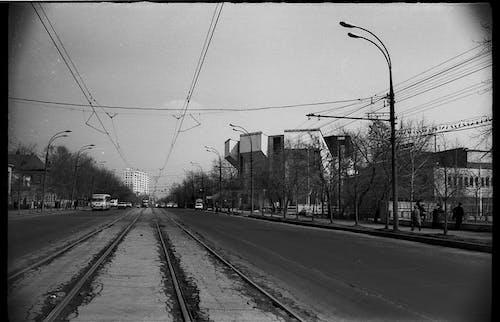 Vehicles riding on city road near tram rails