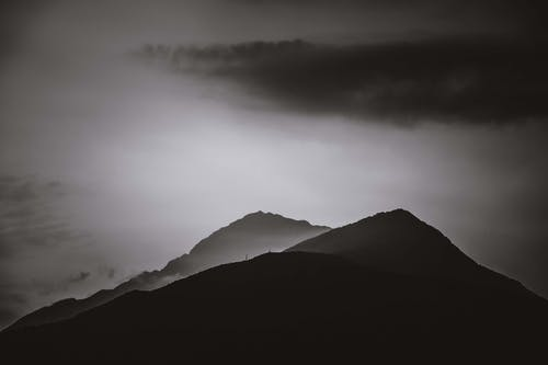 Silhouettes of mountain peaks under cloudy sky