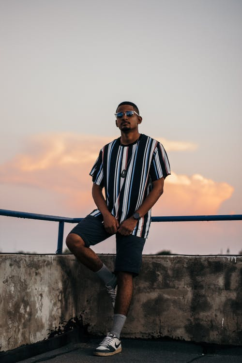 Full body of confident young African American male in trendy outfit and sunglasses relaxing on terrace of aged building against cloudy sunset sky