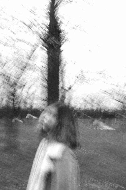 Black and white of defocused female standing on street in park with pillar and trees in daytime in nature outside