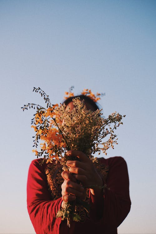 Unrecognizable female in bright apparel covering face with dry autumn bouquet under blue sky