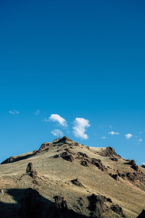 From below of picturesque mountain range with rocky formations against bright blue sky on sunny day