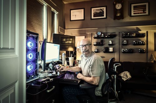 Side view of stressed middle aged male programmer in casual clothes and eyeglasses using various gadgets while working distantly at home