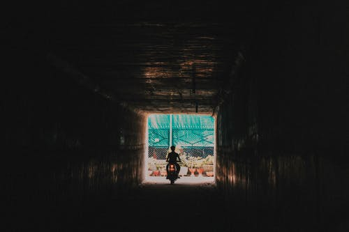 Man in Black Jacket Walking on Tunnel
