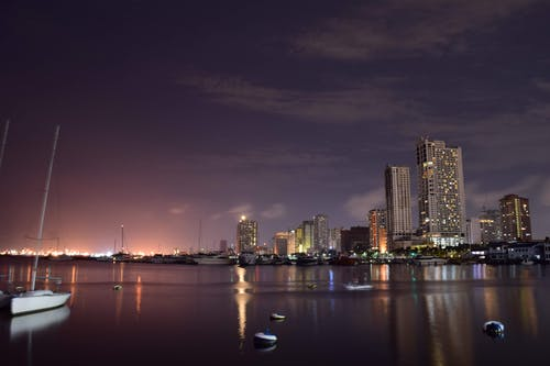 Low angle of modern boats moored in harbor of Manila with contemporary illuminated skyscrapers against evening sky