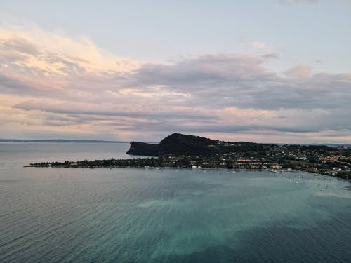 Drone view of rippled sea near mountain with houses under cloudy sky at sunset