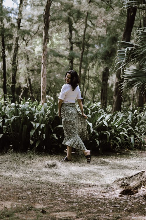 Woman in White Shirt and Black and White Floral Skirt Walking on Dirt Road
