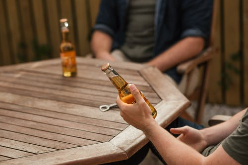 Crop anonymous male partners with glass bottles of alcoholic drink sitting at wooden table on weekend
