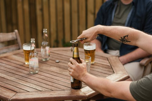 Men opening beer while resting with friend at wooden table