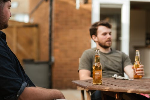 Adult bearded males friends sitting at table with bottles of beer while spending weekend together in yard