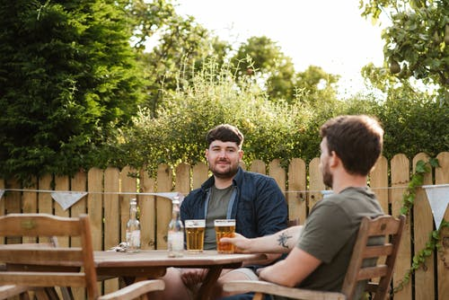 Adult mates chatting while resting with glass of beer at table in backyard in green countryside