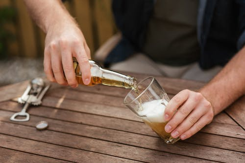 Man pouring beer in glass cup for picnic