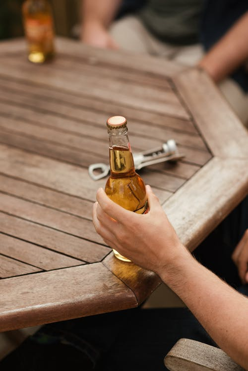 From above of crop anonymous male spending weekend with friend at table with bottle of beer in yard