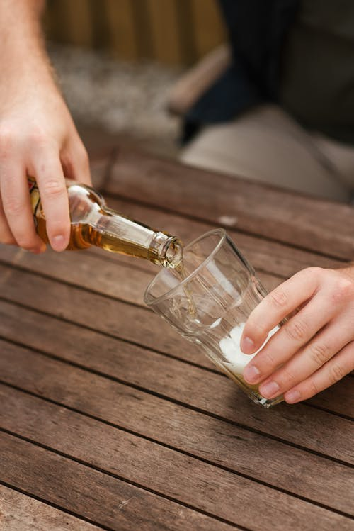 Man filling glass cup with foaming beer