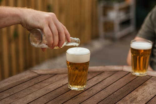 Crop anonymous male pouring beer into glass from bottle while relaxing with friend in backyard