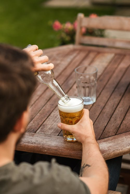Male pouring beer from bottle into glassware