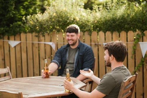 Smiling bearded adult men sitting with glass bottles of beer at wooden table in backyard in green countryside