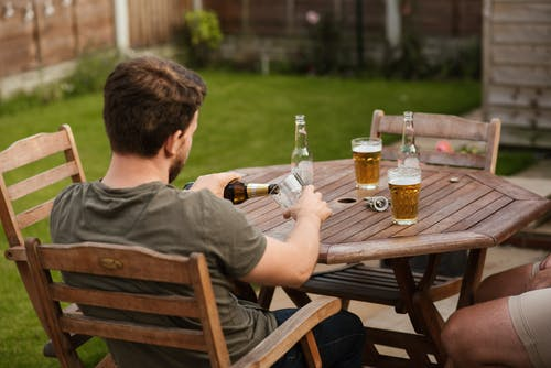 Back view of anonymous male filling glass mug with beer from bottle while chilling with friend at backyard