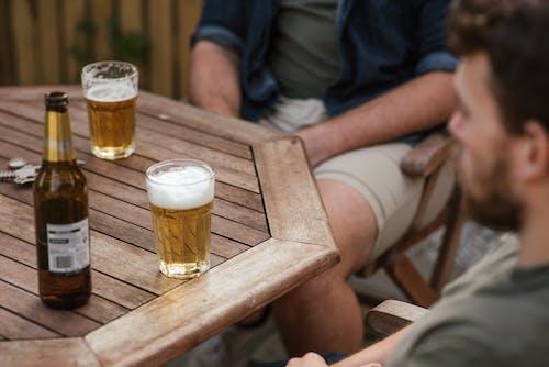 Men having beer during picnic in backyard