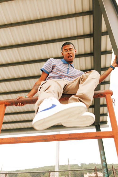 Man in Blue Polo Shirt and White Pants Sitting on Metal Railings