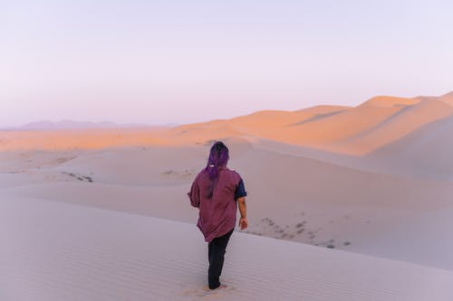 A Woman Standing on the Desert Sand