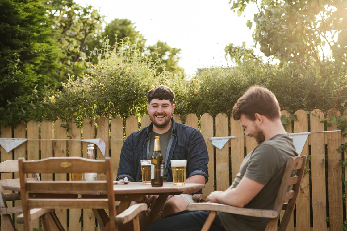 Laughing friends having beer while sitting in chairs at wooden table in backyard and having conversation