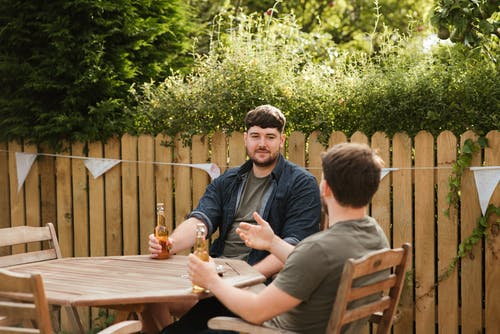 Male friends drinking beer at table in backyard