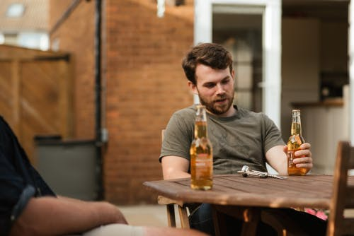 Bearded man having beer with friend