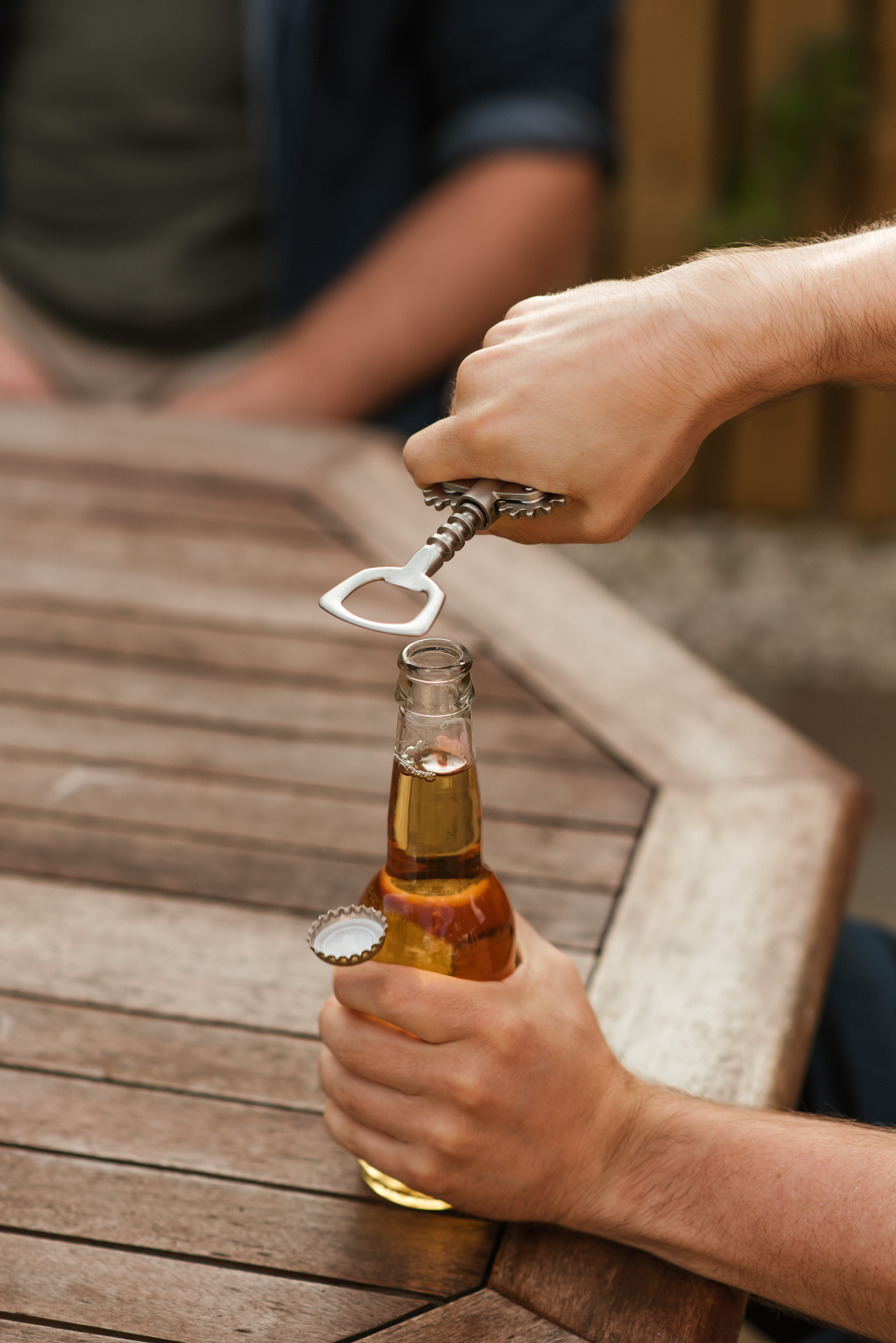 man opening glass bottle of beer with opener