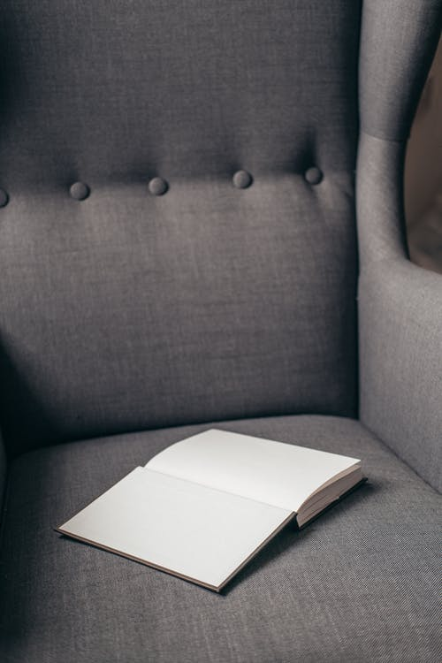 Opened book placed on soft armchair