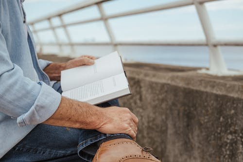 Man reading book on coast of river